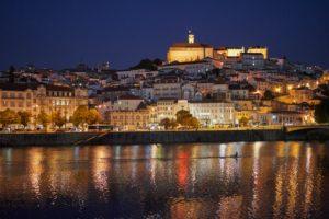 Coimbra illuminated, night, University on hilltop, rower, Mondego River, Portugal