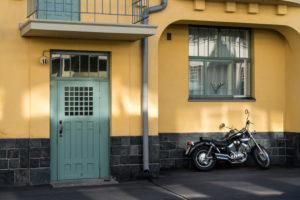 Helsinki, Art Nouveau architecture in Eira district, Juvilakatu, front door, motorcycle