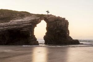 Spanien, Nordküste, Galicien, Nationalpark, Kathedralenstrand, Playa de las Catedrales, Surfer mit Brett auf Felsen