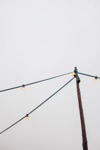 Lichterkette, Glühbirne, Strommasten, grauer Himmel,