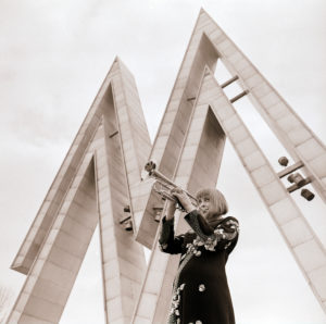 "A young musician from the DFF cult series ""There is music in it"" is blowing the trumpet under the attractive MusterMesse symbols in front of the entrance to the Leipzig exhibition center"
