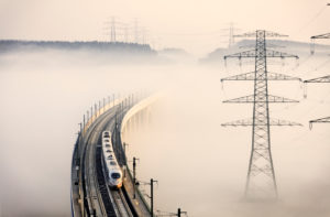 Train, bridge, high-voltage poles, fog