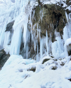 Icicles on the rock face of Urach Waterfall, Swabian Jura, Baden-Wuerttemberg, Germany