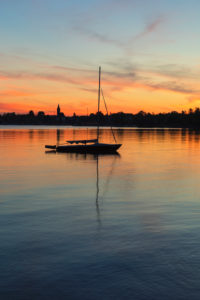 Sailboat at sunset on the Chiemsee, Riemsting, Upper Bavaria, Germany