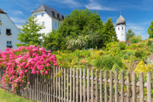 Monastery garden and bell tower of Frauenwörth Monastery on Fraueninsel, Chiemsee, Upper Bavaria, Germany
