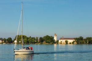 Segelboot auf dem Chiemsee vor der Fraueninsel mit Kloster Frauenwöth bei Sonnenuntergang, Oberbayern, Deutschland