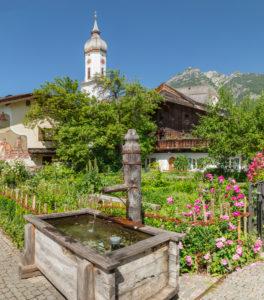 Fountain and Polznkasparhaus and St Martin's Church on Mohrenplatz, Garmisch-Partenkirchen, Upper Bavaria, Bavaria, Germany