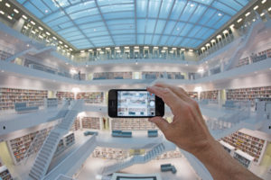 Man close Smartphone takes a photo of balcony hall with staircases of the town library, architects RKW Eun Young Yi, Stuttgart, Baden-Wurttemberg, Germany
