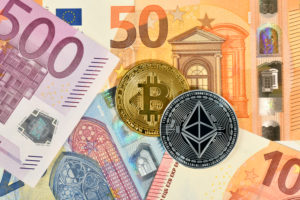 Symbolic image of digital currency, golden physical coin Bitcoin and silver physical coin Ethereum on EURO banknotes