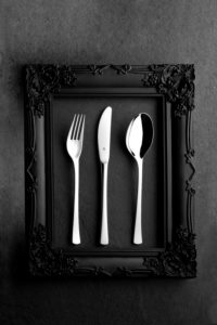 WMF cutlery in a black baroque frame on stone