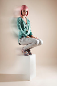 Fashion picture model is standing on big stool, pink Bob hairstyle and lighting effect