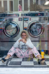 Woman sits in front of washing machine in a launderette in San Francisco