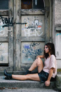 Young attractive brunette woman sits in front of door with graffiti,
