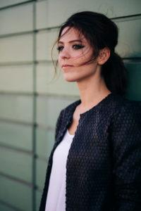 Junge, attraktive, brünette Frau steht vor grünem Garagentor, Halbporträt,