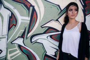 Junge, attraktive, brünette Frau steht vor Graffiti-Wand, Wind weht ihre Haare ins Gesicht,