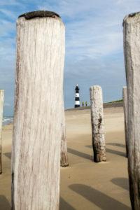 Leuchtturm in Holland, Cadzand, Zeeland, zwei Fahrradfahrer auf der Panoramaroute, Strand mit Buhnen im Vordergrund,
