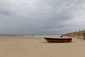 Boot on the beach in Cadzand, by the North Sea, deserted, peaceful which enjoy rest and the vacation,