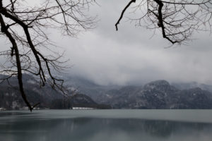 Bergpanorama in Bayern mit Blick auf die Alpen und einen See, Gedeckte Farben, winterlich kaltes Szenario, menschenleer,