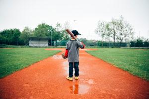 Junge, 5 Jahre alt, beim Baseball spielen auf einem Sportplatz im Regen, Zielstrebigkeit, Training mit Ball, Schläger und Baseballhandschuh, Kräftige Farben, fokussiert, zentriert,