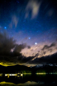 Bergpanorama in Bayern am Fuße der Zugspitze, Blick über See in der Nacht, Sternenhimmel mit Milchstraße, winterlich kaltes Szenario, menschenleer,
