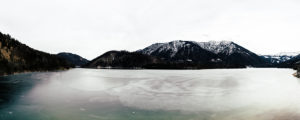 Bergpanorama in Bayern mit Blick auf die Alpen und einen gefrorenen See, gedeckte Farben, winterlich kaltes Szenario, menschenleer,