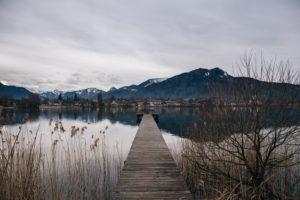 Blick auf Steg und See in Süd-Bayern, Bergpanorama vor gedeckten Farben, grauer Himmel, Winter, schlechtes Wetter und schneeverhangene Berge, einsam, menschenleer,