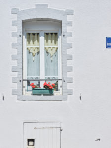Detail view of a facade with a flower box with geraniums on the window in Brest in Brittany.