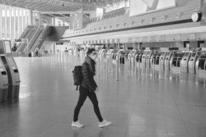 Eine junge Reisende mit Mundschutz durchquert die fast menschenleere Abflugshalle des Terminal 1 am Frankfurter Flughafen, während des allgemeinen Lockdowns in Deutschland wegen der Corona Pandemie.