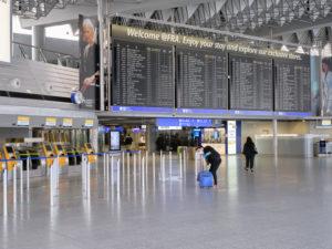 Ein reisender während des Lockdowns wegen der Corona Pandemie in Deutschland am Frankfurter Flughafen mit Gummihandschuhen und Mundschutz.
