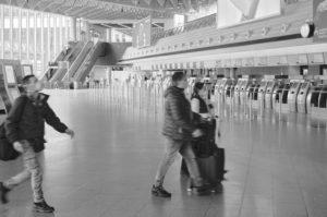 Drei Reisende mit Mundschutz durchqueren die fast menschenleere Abflugshalle des Terminal 1 am Frankfurter Flughafen, während des allgemeinen Lockdowns in Deutschland wegen der Corona Pandemie.