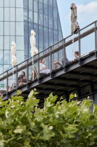 Gäste auf der Aussichtsterrasse des Ausflugslokal Oosten im Frankfurter Ostend, im Hintergrund ist die Fassade der EZB.