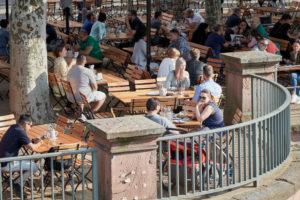 Gäste in einer Gartenwirtschaft an einem sonnigen Nachmittag am Eisernen Steg in Frankfurt.