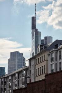 Blick vom Frankfurter Mainufer auf die Commerzbank und den Taunusturm mit den Wohnhäusern am Mainkai im Vordergrund.