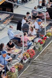 Gäste an einem Sommernachmittag auf einem Restaurantschiff auf dem Main in Frankfurt.