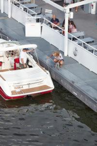 Ein Paar legt mit seinem Motorboot von der Außenseite eines Ausflugsschiffs auf dem Main in Frankfurt ab.