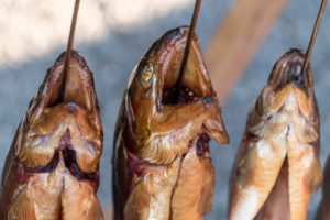 Steckerlfisch' (fish grilled on a stick) at the Oktoberfest, Munich, Bavaria, Germany