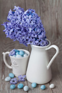 Hyacinth flowers in vase and Easter eggs in coffee cup, still life