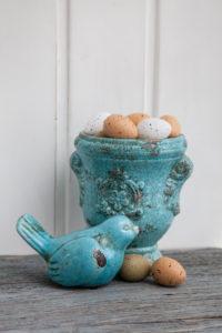 Easter still life, Easter eggs in ceramic pot and bird figure, close-up, still life