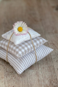 Daisies on pile of pillows, Bellis perennis, close-up, still life
