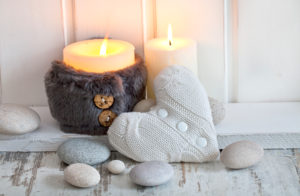 rustic Christmas or autumn still life with candles, knitted heart and pebble across white wood