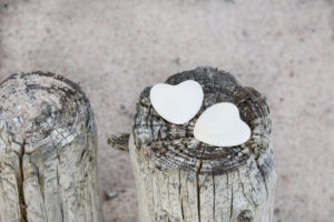 two white stone hearts on weathered wooden poles on a sandy beach