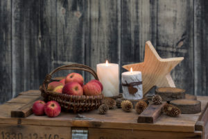 rustic still life hygge style with wooden stars, apples and candles on old crate