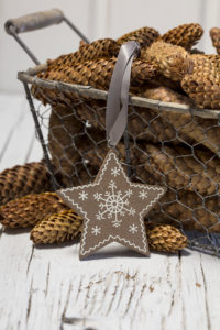 rustic Christmas still life with vintage wire basket full of pine cones and wooden star ornament