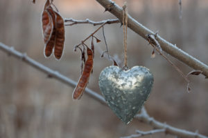 simple tin heart ornament hanging outside on a cold autumn day