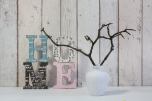 decoration in a white interior with wooden letters of word home and simple twigs in a vase