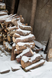 snow covered pile of firewood in front of a barn