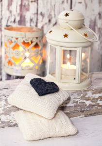 A rustic winter or Christmas deocoration in a white interior, with lanterns, felt heart and knitted deocor objects