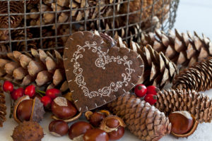 rustic autumn decoration with felt heart and pine cones and chestnuts