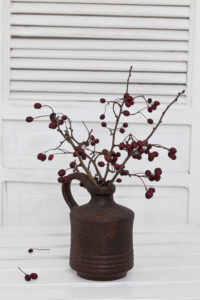 A rustic winter or Christmas deocoration in a white interior, with red berry twigs in a brown vase