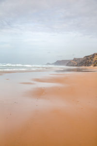 lonely, shallow sandy beach  at the wild west coast of the portuguese algarve with rough cliffs